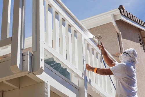 Patios Remodeling - House Painter Wearing Facial Protection Spray Painting A Deck of A Home.